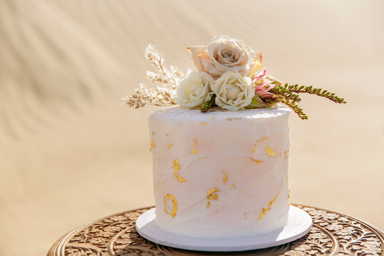 styled-shoot-white-white-weddings-bohemian-desert-style-elopement-tips-cake-gold-foil-roses-sand-dunes