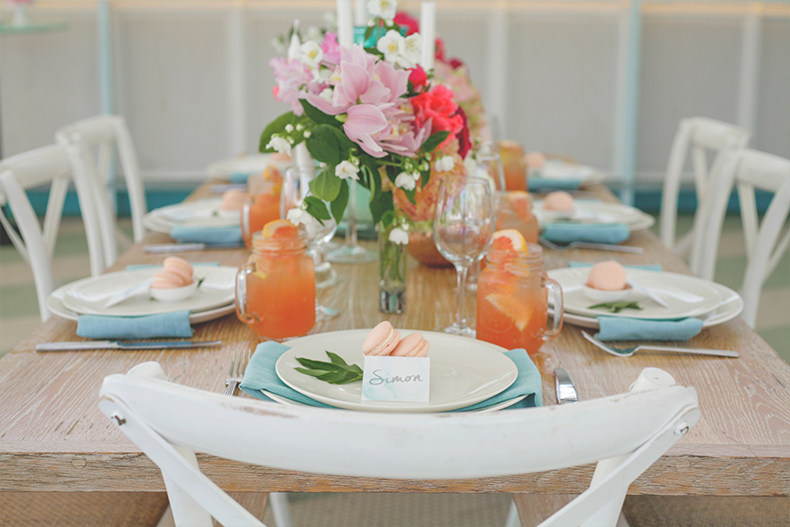 styled-shoot-watsons-bay-sydney-summer-wedding-styling-white-white-weddings-and-events-tablescapes-hampton-chairs-white-colourful-florals-orange-cocktails-grapefruit-blue-napkins-macarons