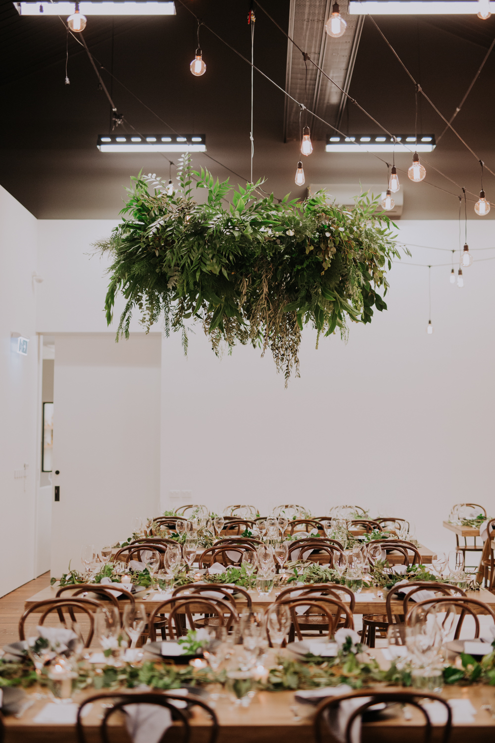 white+white weddings and events carrie and jay real wedding styling bentwood chairs banquet tables timber rustic studio warehouse venue hanging foliage