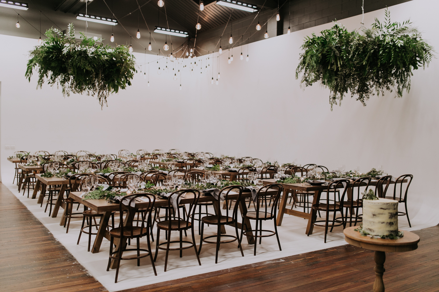 white+white weddings and events carrie and jay real wedding styling bentwood chairs banquet tables timber rustic studio warehouse venue hanging greenery