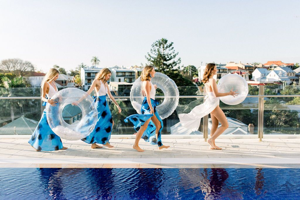 styled shoot white+white weddings and events get robed modern pink blue and white feather filled floaties bride tribe