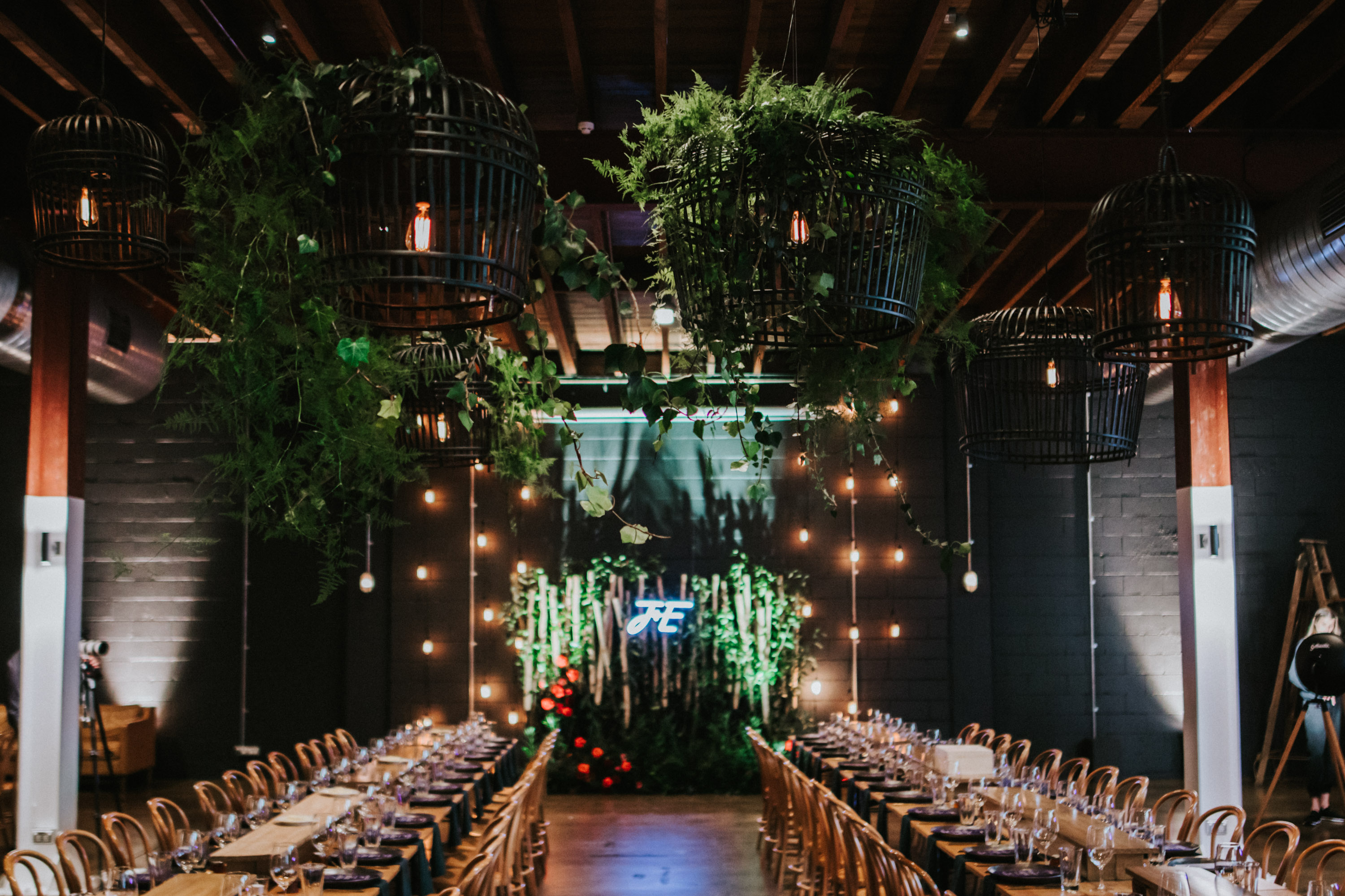 white+white weddings and events the wedding school emily and jack lightspace wedding greenery ceremony florals suspended hanging bentwood chairs asha reception table table number whole room long tableware neon sign hanging roof full room