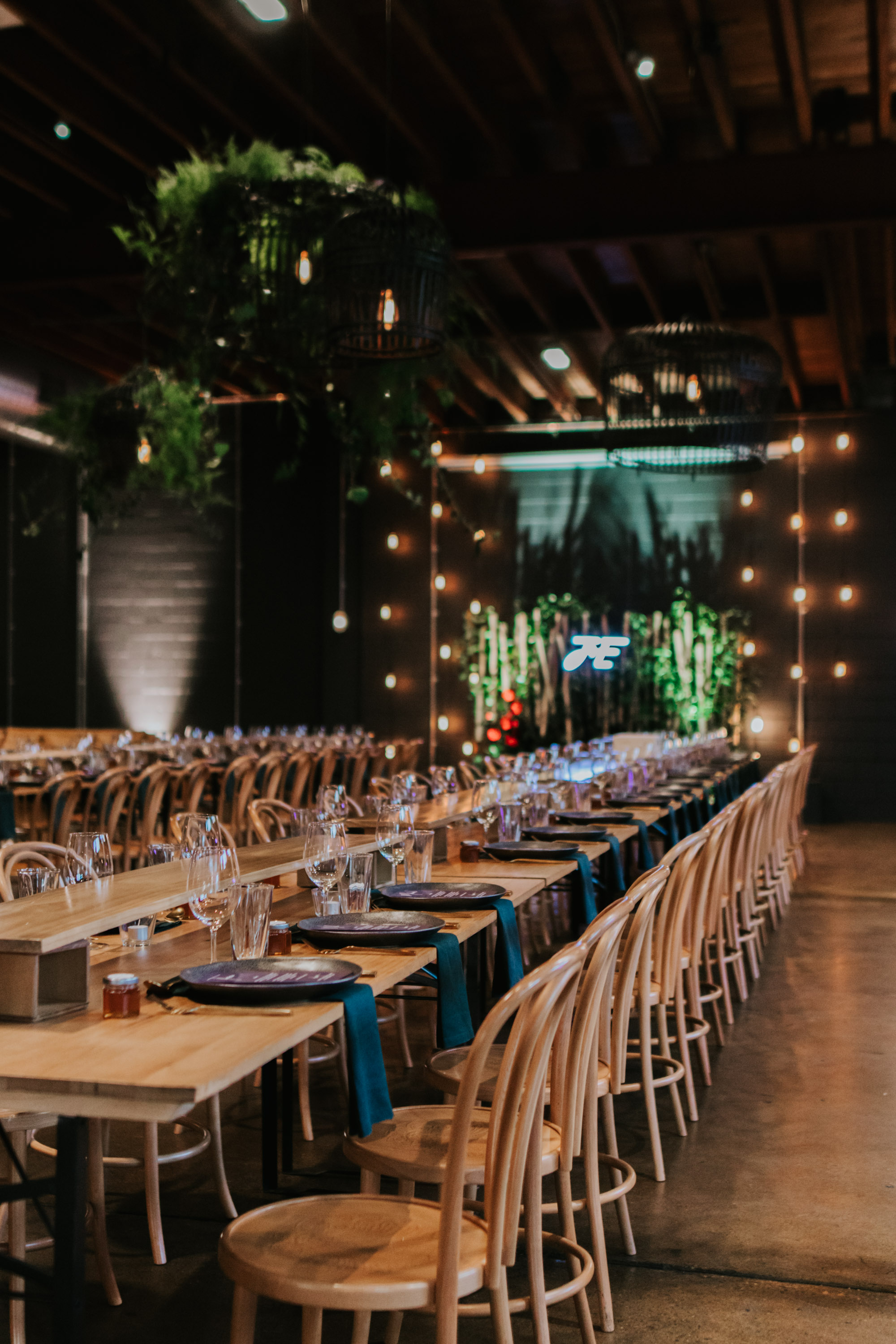 white+white weddings and events the wedding school emily and jack lightspace wedding greenery ceremony florals suspended hanging bentwood chairs asha reception table table number whole room long